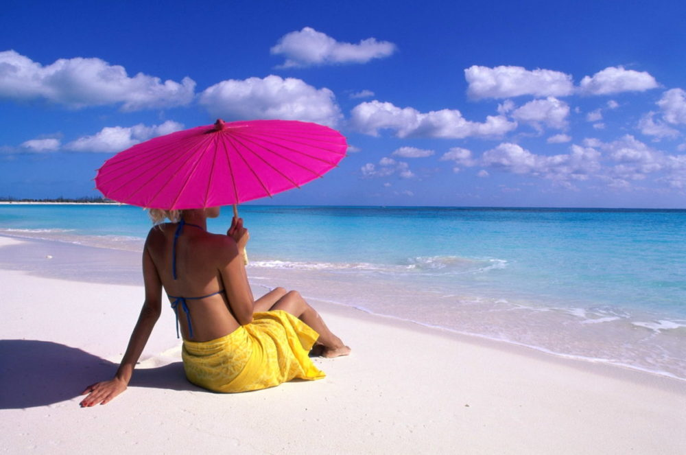 Rear view of a woman sitting with a parasol on the beach
